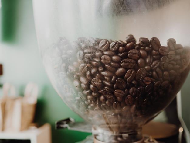 Sluit omhoog van koffiebonen in de machine met groene muur als achtergrond.
