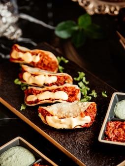Sluit omhoog van kruidige minitaco's die met spaanse pepersdeeg worden gediend