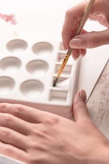Sluit omhoog van kunstenaar gebruikend palet en borstel voor het schilderen