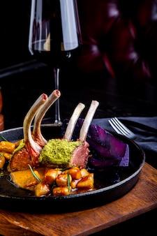 Sluit omhoog van lamskoteletten met groenten met een saus van karamel, peper en kruiden in restaurant het plaatsen.
