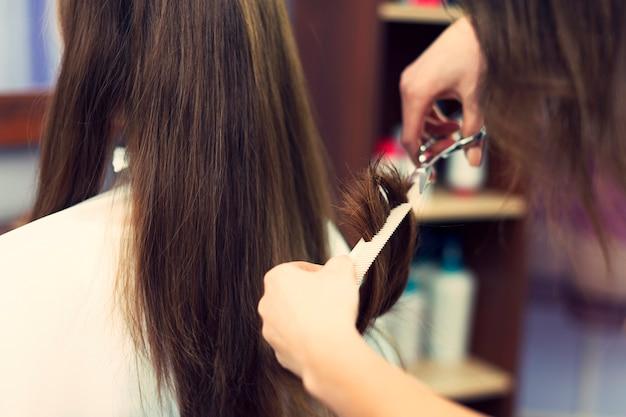 Sluit omhoog van lang haar dat door kapper wordt gesneden