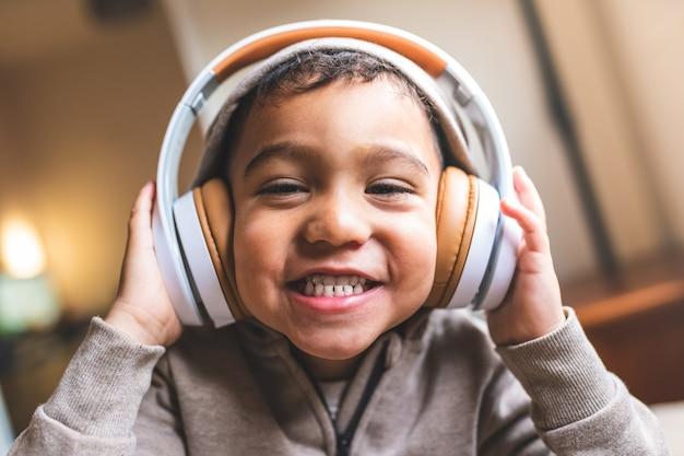 Sluit omhoog van latijns-amerikaanse het luisteren van de jongen muziek op hoofdtelefoons.