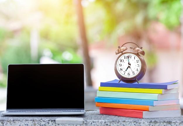 Sluit omhoog van lege laptop op bureau met roze die wekker op de boeken wordt geplaatst.