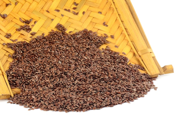 Sluit omhoog van lijnzaad in houten mand op witte oppervlakte