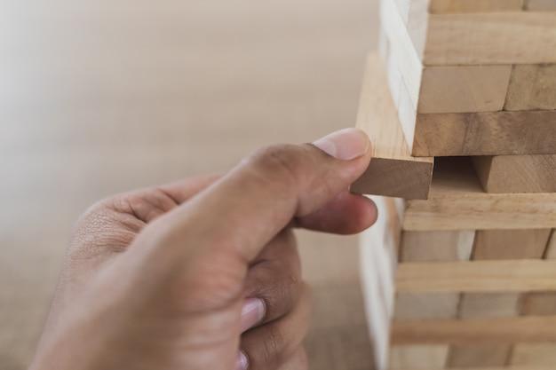 Sluit omhoog van linkerhand van de mens neem de houten stok uit het zijaanzicht houten van de toren (jenga)