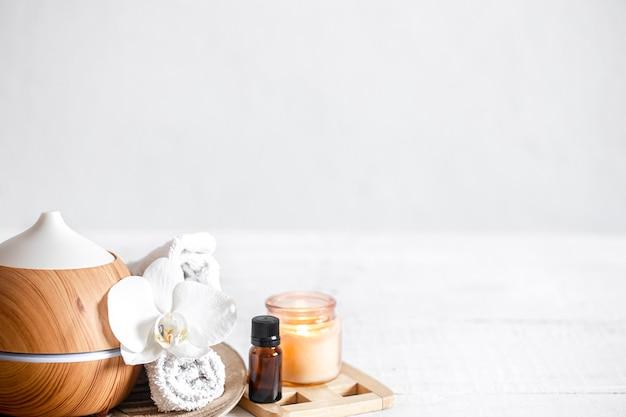 Sluit omhoog van luchtbevochtiger, handdoek, aromatische olie en orchideebloem. aromatherapie en zorg en gezondheid concept achtergrond