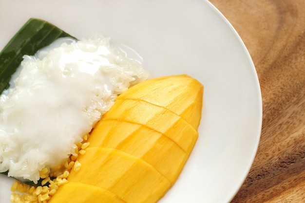 Sluit omhoog van mango kleverige rijst op witte plaat, populair traditioneel zoet dessert van thailand.