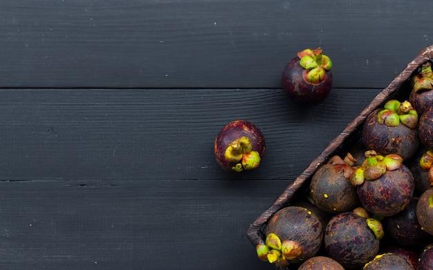 Sluit omhoog van mangostanfruit op zwarte houten lijst