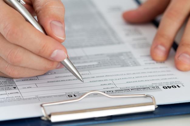 Sluit omhoog van mannelijke accountant die berekeningen maakt. man schrijven iets zittend op zijn kantoor. invullen van individueel aangiftebiljet 1040, maken van financieel rapport, huisfinanciën of economieconcept