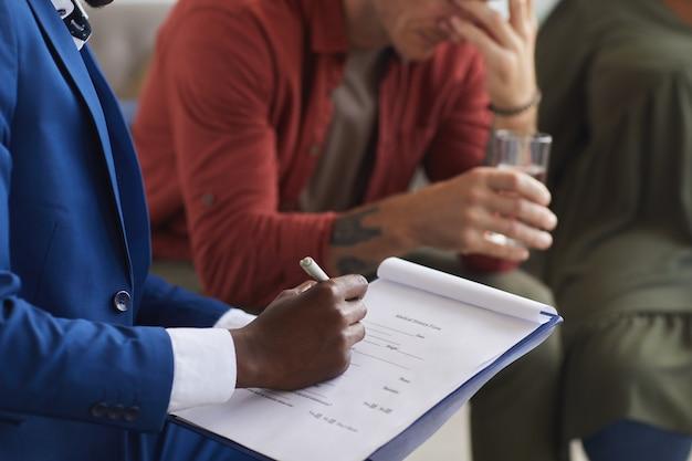 Sluit omhoog van mannelijke afro-amerikaanse psycholoog die op klembord schrijft terwijl het leiden van steungroepsessie, exemplaarruimte