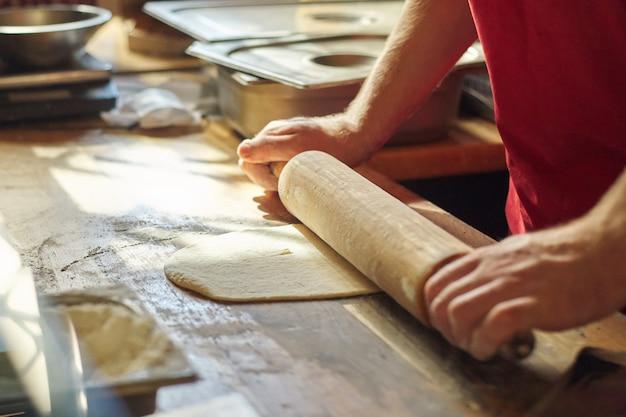 Sluit omhoog van mannelijke bakkershanden met bloemkok ontwikkelen het deeg met deegrol