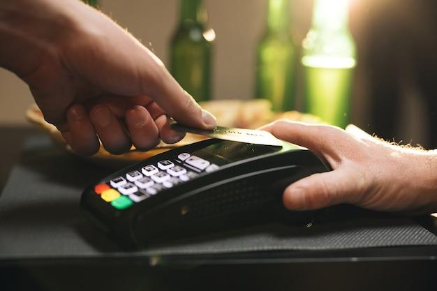 Sluit omhoog van mannelijke greep in hand draadloze moderne bankbetalingsterminal