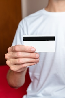 Sluit omhoog van mannelijke hand die een witte creditcard houdt.