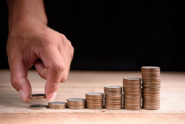 Sluit omhoog van mannelijke hand die gouden muntstukken, bedrijfsfinanciën en het geldconcept stapelen, sparen geld voor te bereiden