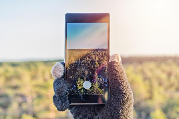 Sluit omhoog van mannelijke hand houdend slimme telefoon en nemend foto