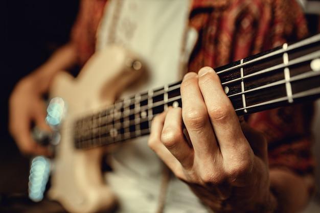 Sluit omhoog van mannelijke hand spelend elektrische gitaar in dark