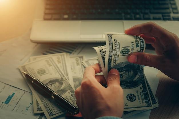 Sluit omhoog, van mannelijke handen die dollarrekeningen tellen.