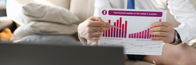 Sluit omhoog van mannelijke handen die klembord van echte financiële statistiek op betreffende markt houden