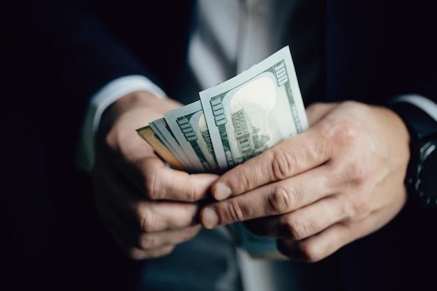 Sluit omhoog van mannelijke handen tellend dollarrekeningen