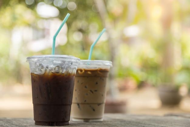 Sluit omhoog van meeneem plastic kop bevroren zwarte koffie (americano) en bevroren koffie latte op houten lijst in tuin met exemplaarruimte