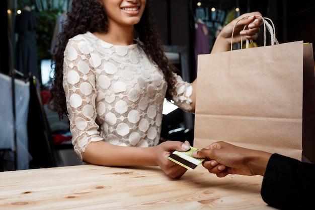 Sluit omhoog van meisje betaalend voor aankopen in winkelcomplex.