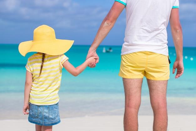 Sluit omhoog van meisje die haar vaderhand op het strand houden