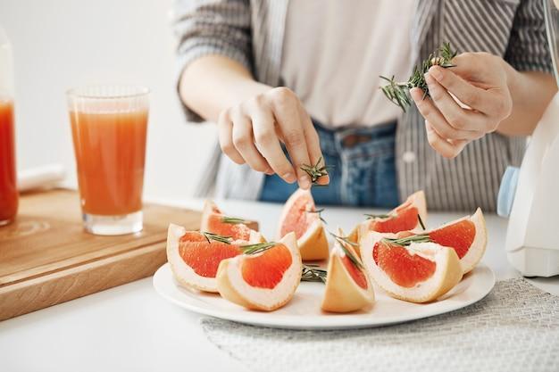 Sluit omhoog van meisje die plaat met gesneden grapefruit en rozemarijn verfraaien. fitness voeding concept. kopieer ruimte.