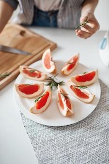 Sluit omhoog van meisje die plaat met gesneden grapefruit en rozemarijn verfraaien. gezonde voeding concept. kopieer ruimte.