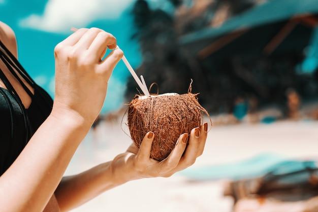 Sluit omhoog van meisje het drinken cocktail in kokosnoot terwijl status op het strand.