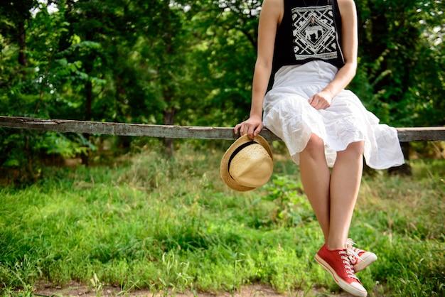 Sluit omhoog van meisje in rode keds zittend op bank.