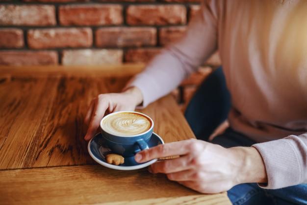 Sluit omhoog van mens het drinken koffie in cafetaria in ochtend