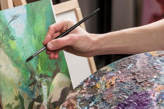 Sluit omhoog van mens het schilderen