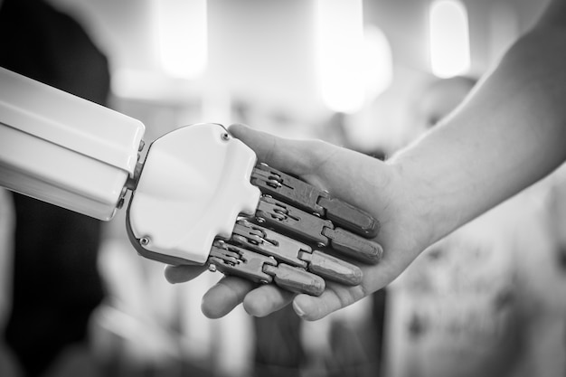 Sluit omhoog van mens het schudden handen met een robot
