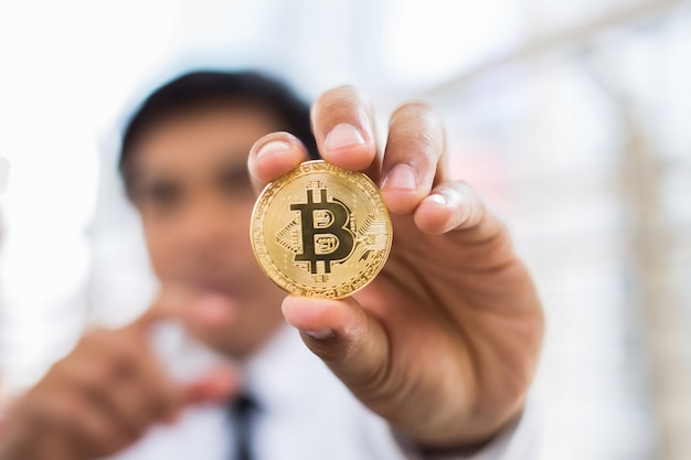 Sluit omhoog van menselijke hand die bitcoin toont.