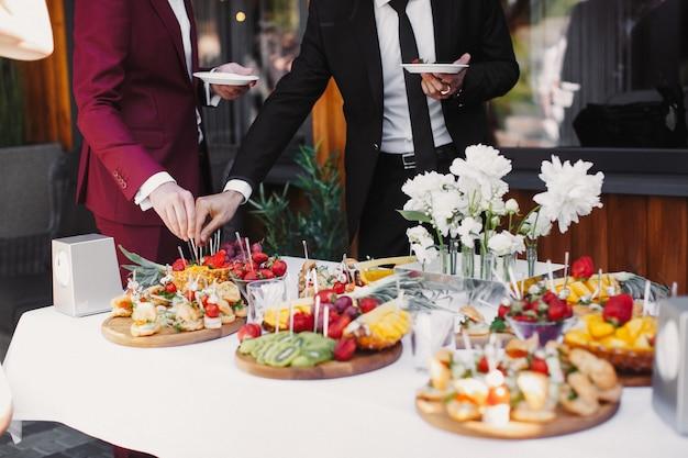 Sluit omhoog van mensen die de vruchten in buffet van restaurant dienen