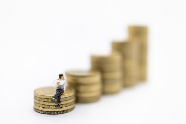 Sluit omhoog van mensen die van het zakenman de miniatuurcijfer en een krant op stapel gebruikte gouden muntstukken zitten lezen