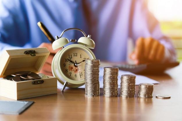 Sluit omhoog, van mensenhand die de muntstukken op de lijst in zijn bureau zetten.
