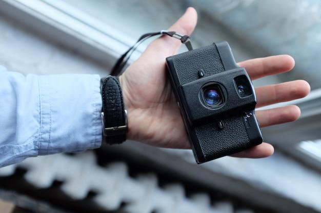 Sluit omhoog van mensenhand die retro camera houden