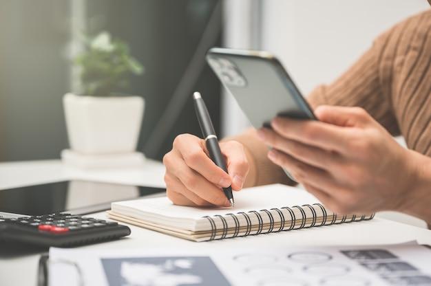 Sluit omhoog van mensenhandwerk met calculator voor zaken en financiën.