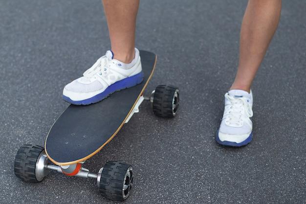 Sluit omhoog van mensenvoeten op modern elektrisch skateboard op straat op asfalt.