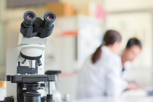 Sluit omhoog van microscoop bij het bloedlaboratorium, conceptenwetenschap en technologie
