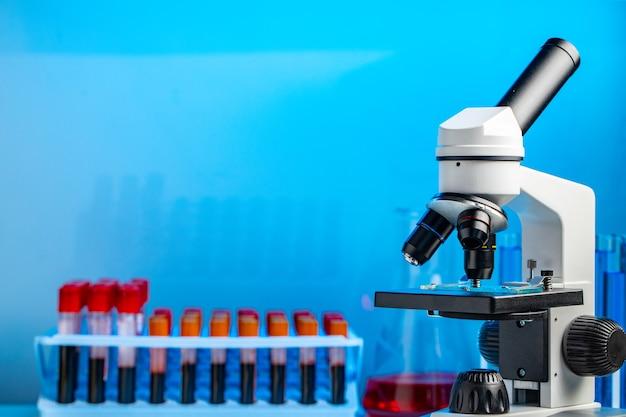 Sluit omhoog van microscoop en dienblad met bloedsteekproeven op blauwe achtergrond