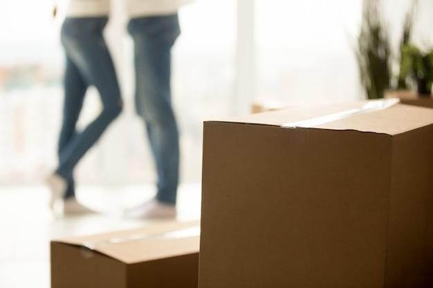 Sluit omhoog van millennial paar die zich aan nieuw huis met dozen bewegen
