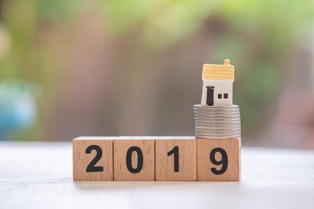 Sluit omhoog van miniatuurhuismodel op stapel zilveren muntstukken op het houten bloknummer van 2019.
