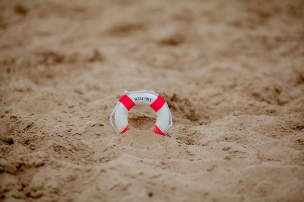 Sluit omhoog van miniatuurreddingsboei op het zand