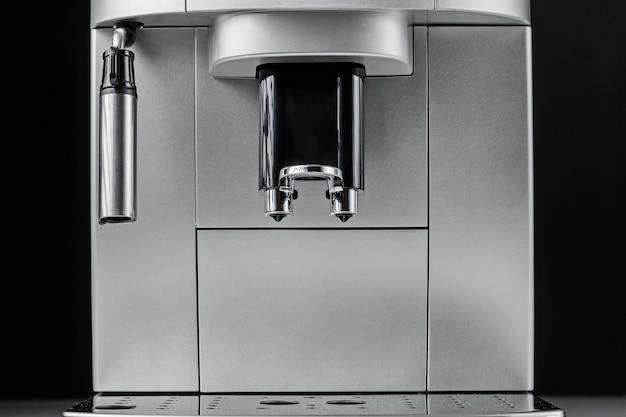 Sluit omhoog van moderne koffiemachine bij zwarte achtergrond