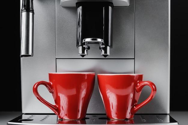 Sluit omhoog van moderne koffiemachine en twee rode koppen bij zwarte achtergrond