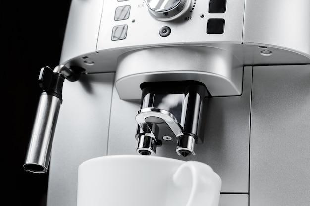 Sluit omhoog van moderne koffiemachine en witte kop bij zwarte achtergrond