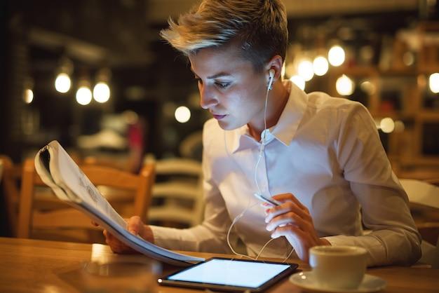 Sluit omhoog van modieus studentenmeisje lerend van het boek terwijl het zitten in een koffie met tablet en oortelefoons in de nacht