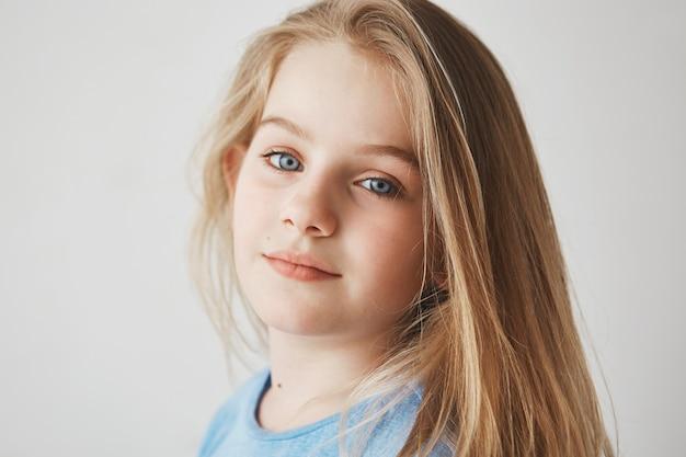 Sluit omhoog van mooi blondemeisje die met heldere blauwe ogen hoofd in drie kwart houden, stellend voor foto met zachte glimlach.